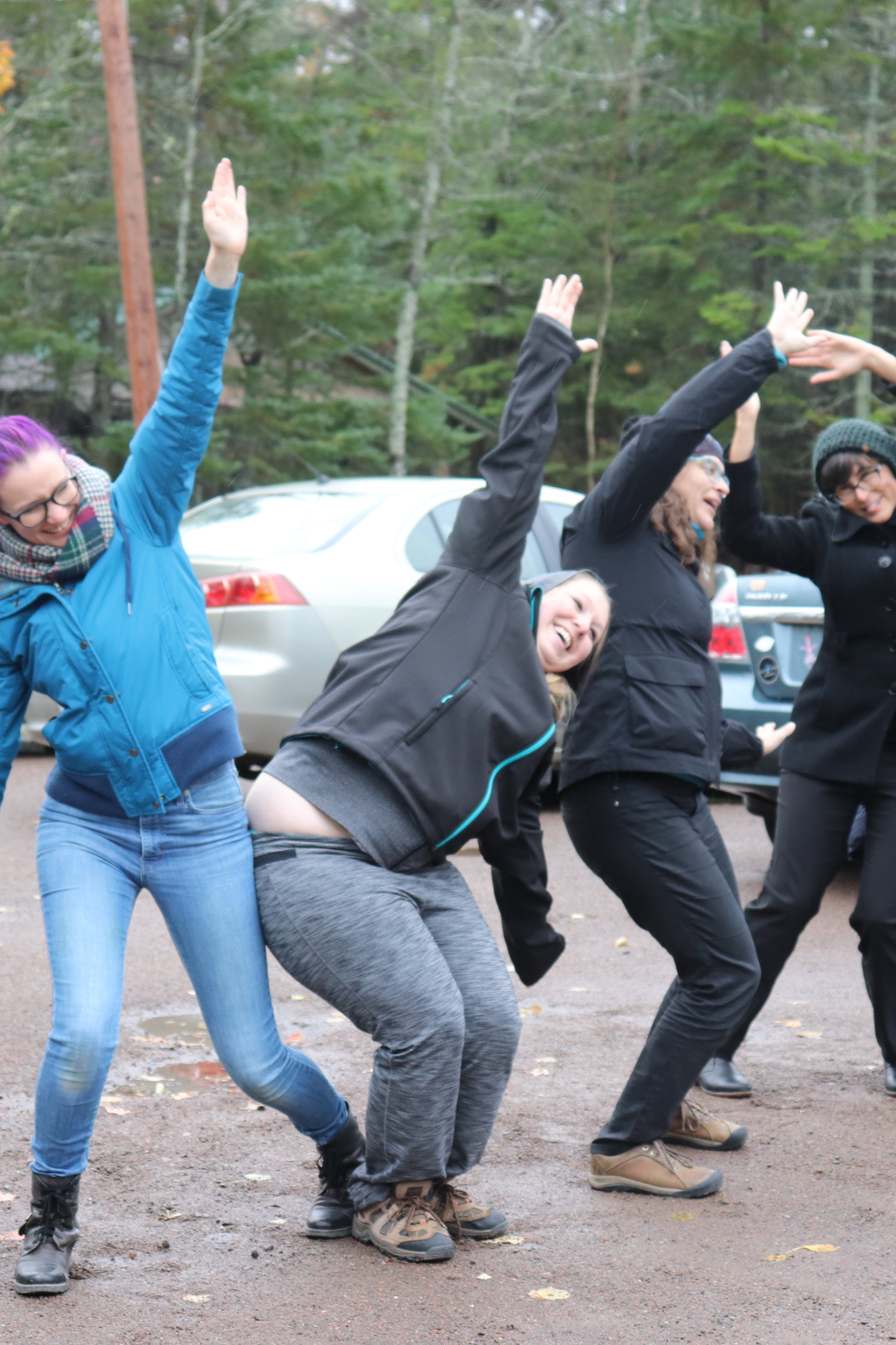 Four adults in casual outdoor clothing are smiling and laughing while making large dramatic gestures with their arms